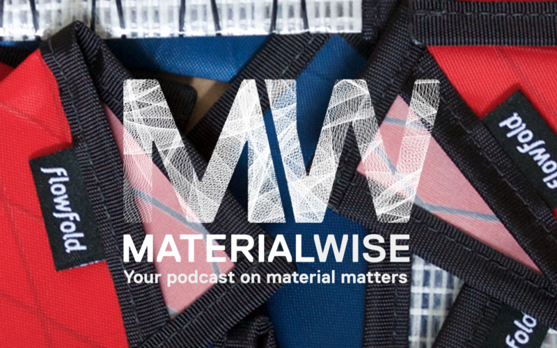 Flow fold wallets with red, pink, blue and black boarders a texture behind the material wise podcast logo.